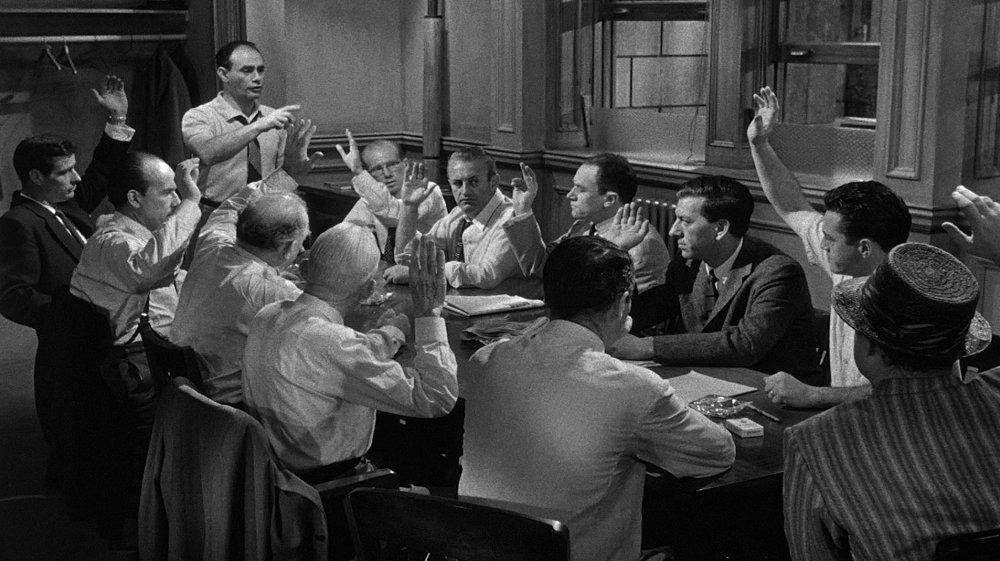7. Lumet's initial stylistic choice, like the opening shot, is a wide-angle lens angled downwards that gives the whole jury focus and the room ample space to clearly show 11 hands raised in near-unanimous agreement of a guilty verdict.