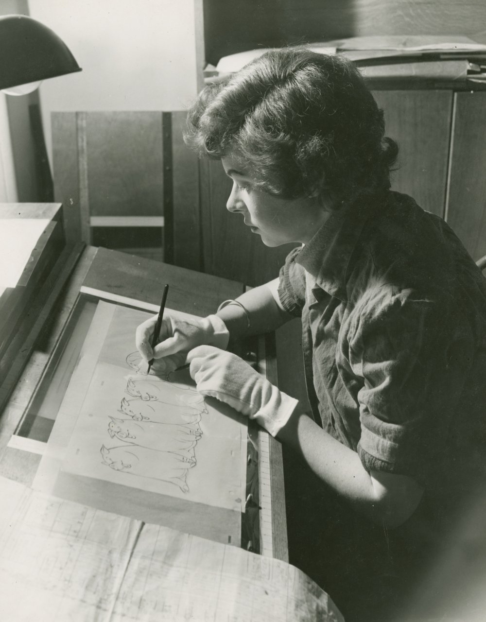 <strong>Alma Coles</strong>, ink and paint artist, Animal Farm (1954). Coles is at her desk working on pen and ink drawings of Snowball the pig. Animal Farm was the first postwar animation feature made in Britain