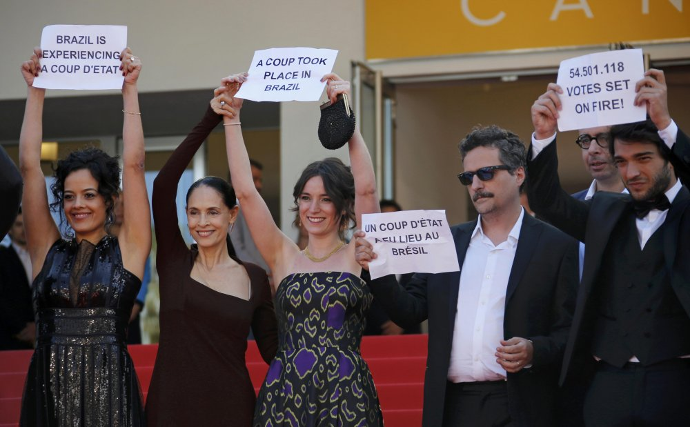 The cast of Aquarius and its writer-director Kleber Mendonça Filho protest the removal from power of Brazil's president Dilma Roussef on the red carpet of Cannes, May 2016
