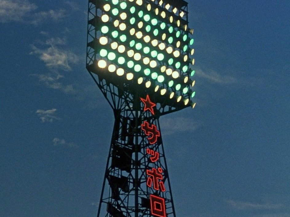 A striking shot of baseball stadium floodlights, nicely undercut moments later when its ageing male characters are shown to be watching the game on television