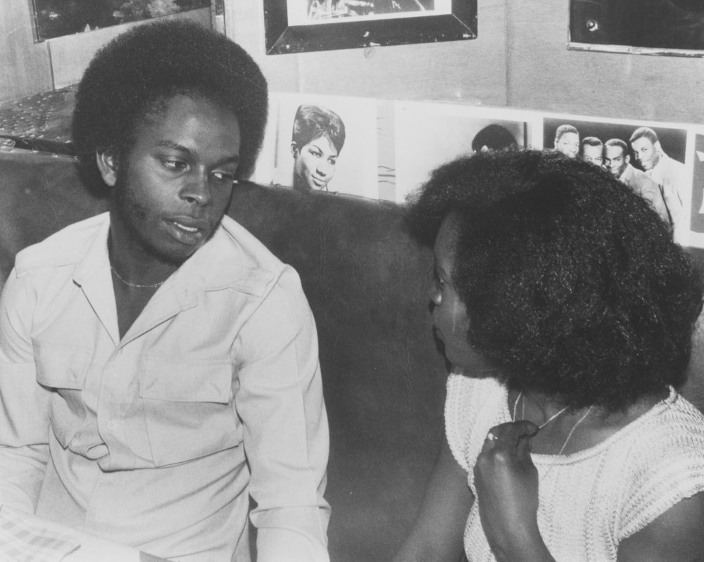 Del and Pat chat in a restaurant. On the wall in the background is a photo gallery of soul artists, including Aretha Franklin