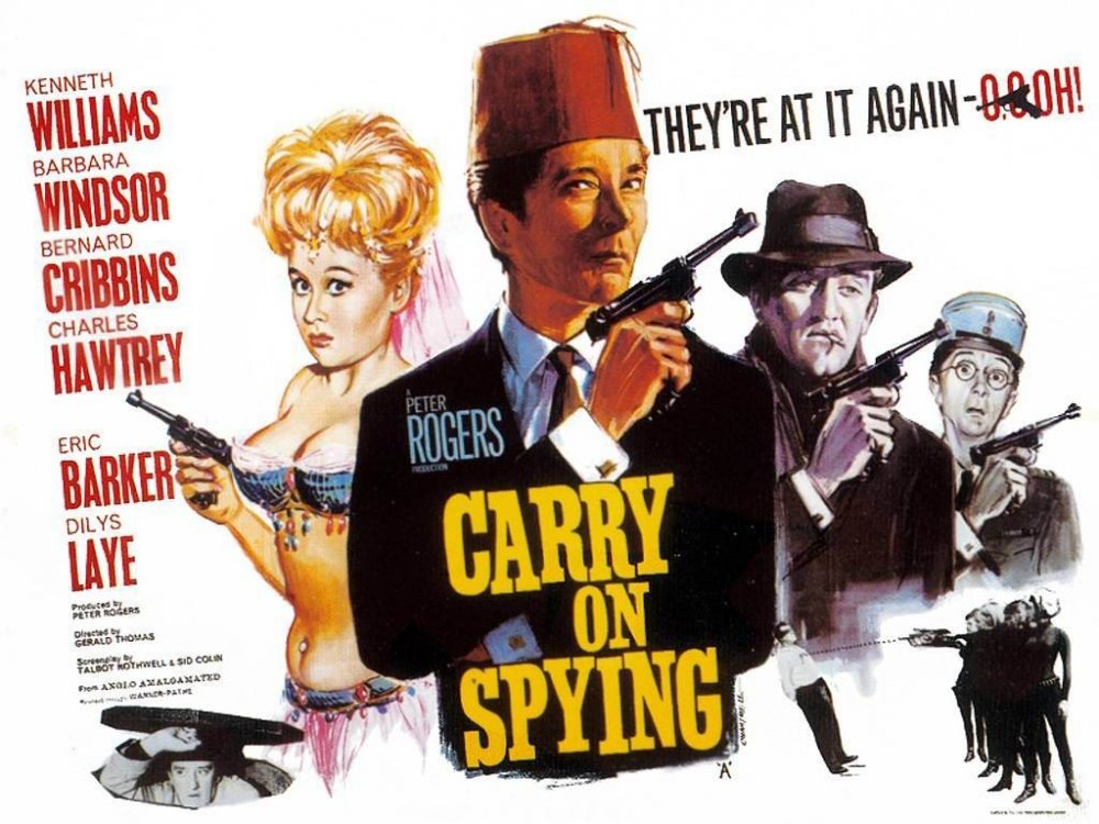 <strong>Carry On Spying (1964)</strong>. Design and illustration by Tom Chantrell. They're at it again – oooh! This is classic Chantrell, quite distinct in style from the later Fratini/Putzu caricatures – sharply done, atmospheric portraits in a neatly balanced layout, with Barbara Windsor's warm flesh-tones deliberately catching the eye. Kenneth Williams' Connery pose is insolently inspired (United Artists fortunately didn't sue), and the bright yellow title on the black jacket the perfect finishing touch. This is not a poster you're likely to walk past and ignore