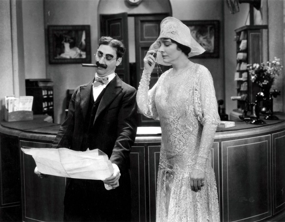 Margaret Dumont as Mrs Potter, inspecting Mr Hammer's wares in The Cocoanuts.