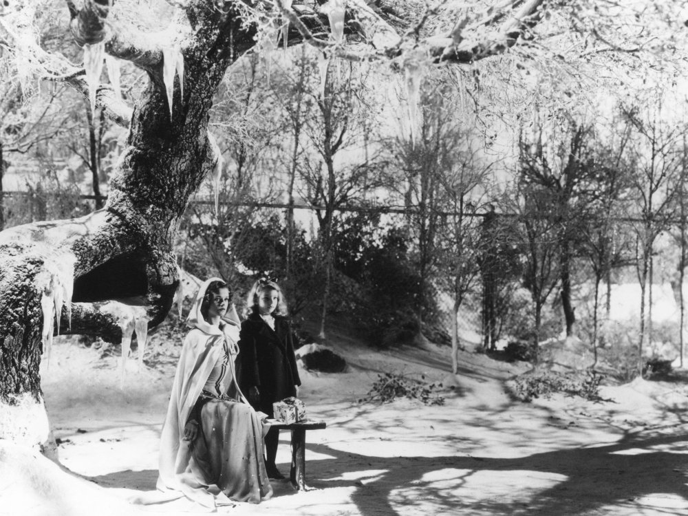 Producer Val Lewton has thickly laid on the winter atmospherics for this scene in 1944 horror-fantasy The Curse of the Cat People. Irena (Simone Simon) returns from the dead suitably attired for the cold in this Salem-styled hooded shawl