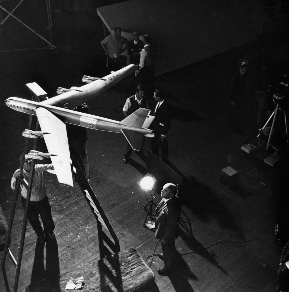 Wally Veevers (special effects) stands underneath the model B-52.
