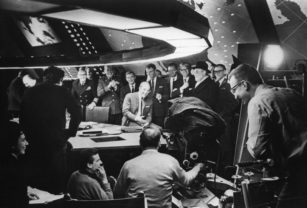 Peter Sellers (centre) shares a joke with cast and crew in Ken Adam's famous war room set.