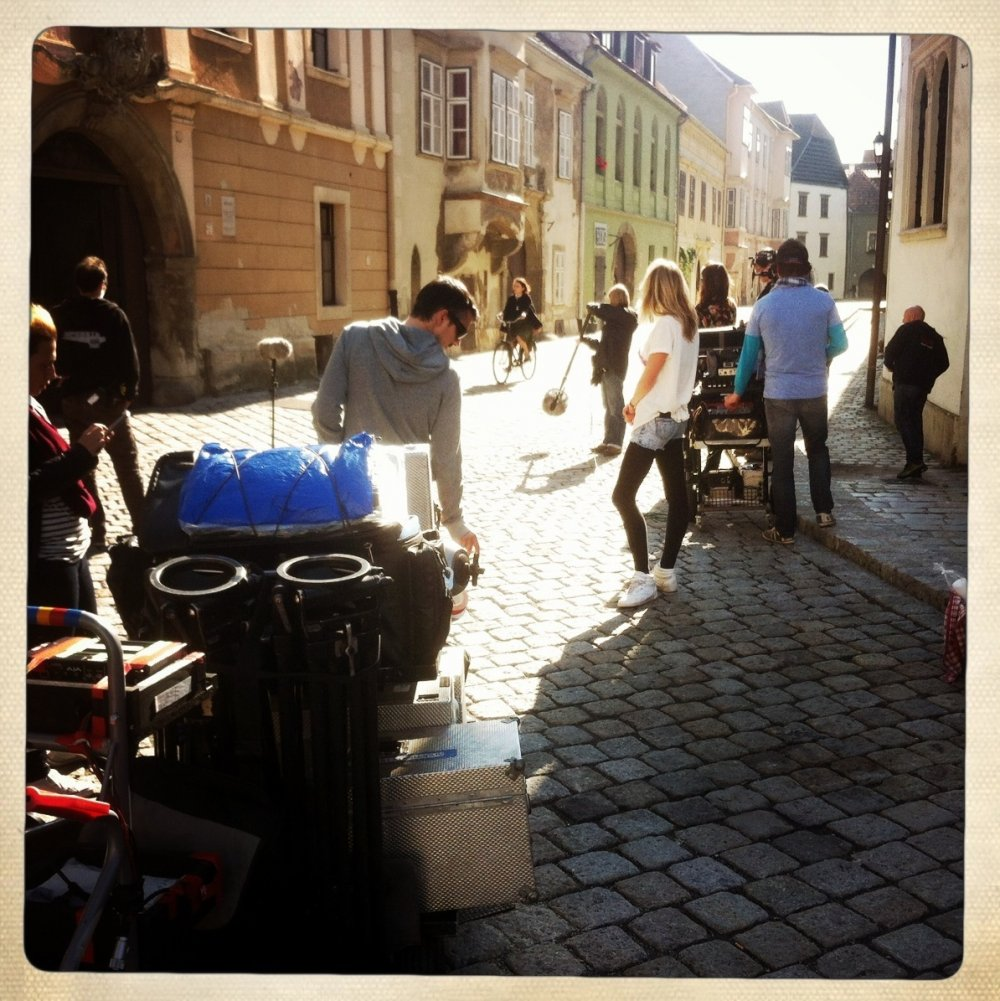 The crew watches as Chiara D'Anna cycles down a paved street in Sopron