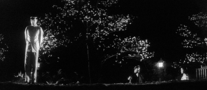 This shot, in which Nanbu is left shamefaced after being discovered promenading with Michiko by school bully Takuan, highlights Suzuki's unorthodox approach to positioning characters within the frame: Nanbu stands separated from the others by a gulf of blackness peppered with decorative cherry blossoms