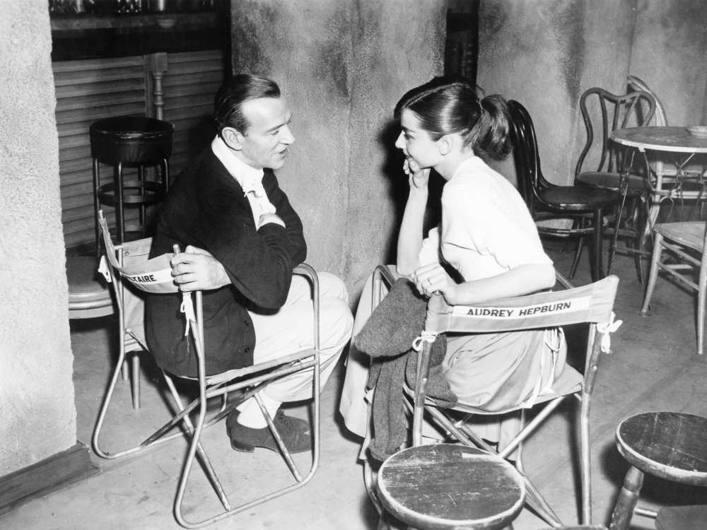 Astaire and Hepburn chat on the set for a boho Parisian café