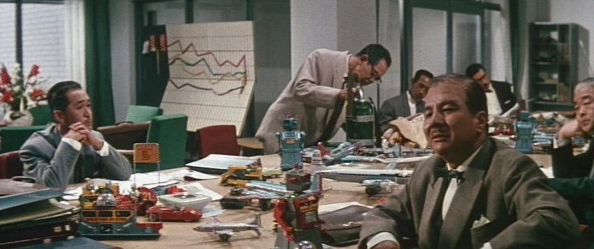 Garish colours abound in the office interiors, crammed with ranks of white-collar workers and jumbled arrangements of calendars and sales graphs. The depth-of-field constraints of anamorphic lenses encouraged an aesthetic of flatness, longer takes and a new way of 'reading' the screen. Note the horizontal positioning of the characters