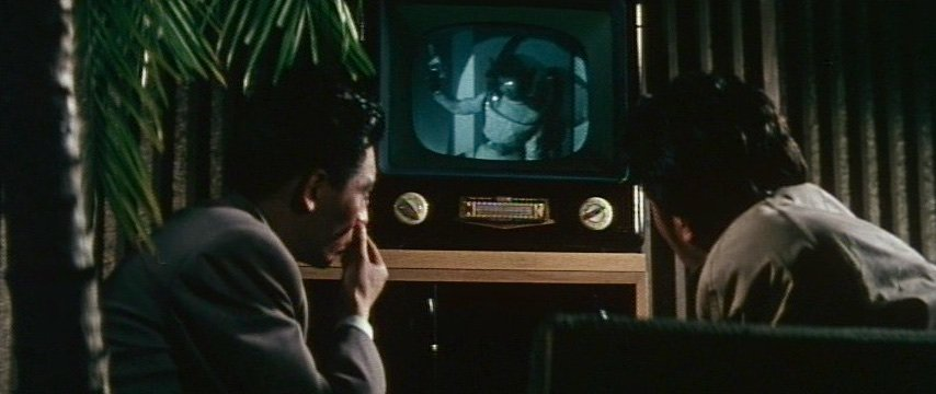 'I like TV, no one demands their money back', a character observes at one point, but the appearance of small TV sets in many scope features of this era underscores cinema's superiority in terms of spectacle. Kyoko's appearance in World Caramel's advert playing in the background of this bar scene signals television's role in her ascendence from street urchin to star