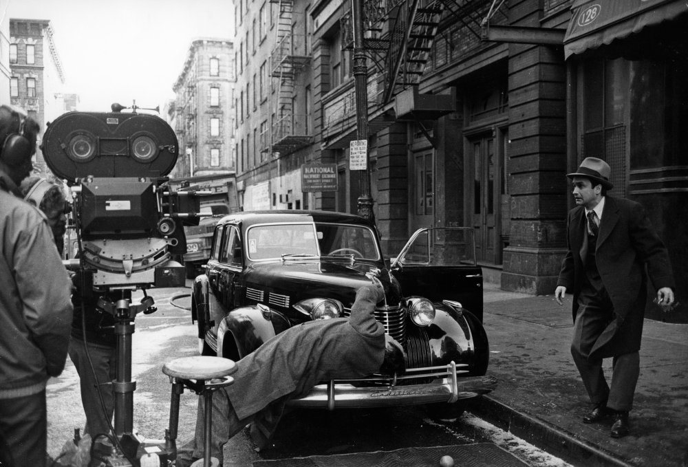 The crew films a street assassination stunt, with John Cazale as Fredo Corleone, the weak link in the Corleone family, watching helplessly from the curb
