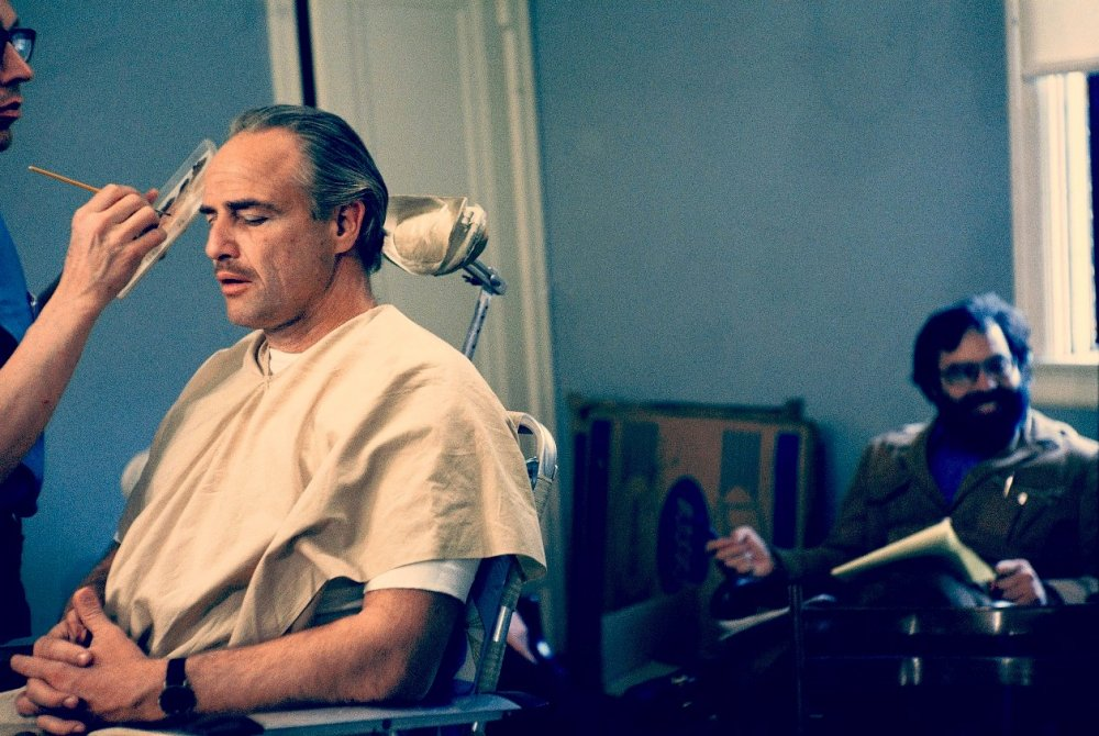 Marlon Brando gets made up as Mafia family patriarch Don Corleone in The Godfather (1972), while director Francis Ford Coppola waits in the background