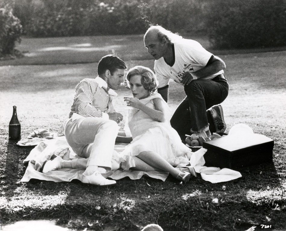 Director Jack Clayton discusses a scene with Robert Redford (Gatsby) and Mia Farrow (Daisy) during filming of The Great Gatsby (1974)