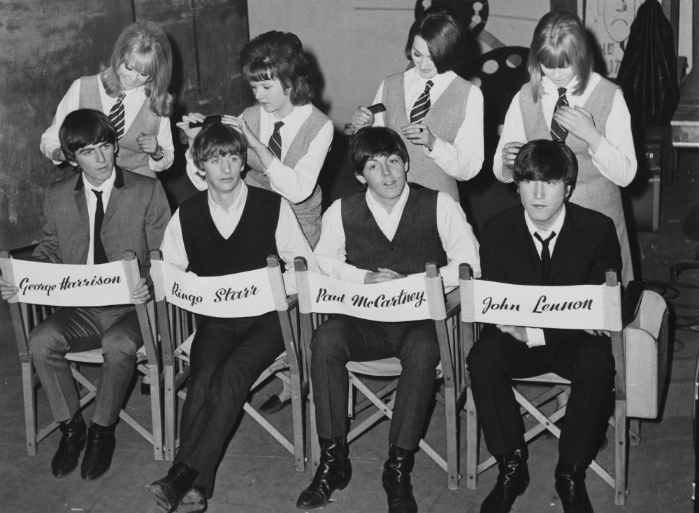 'Mop tops' promotional photograph. The press campaign book caption for this photograph comments on The Beatles famous 'mop top' hair styles. In the film, one witty line has a journalist asking George 'What would you call that haircut you're wearing?', to which George replies: 'Arthur'. Doing George Harrison's hair in this shot is Pattie Boyd, who played a small part as a schoolgirl in A Hard Day's Night and would marry Harrison in 1966