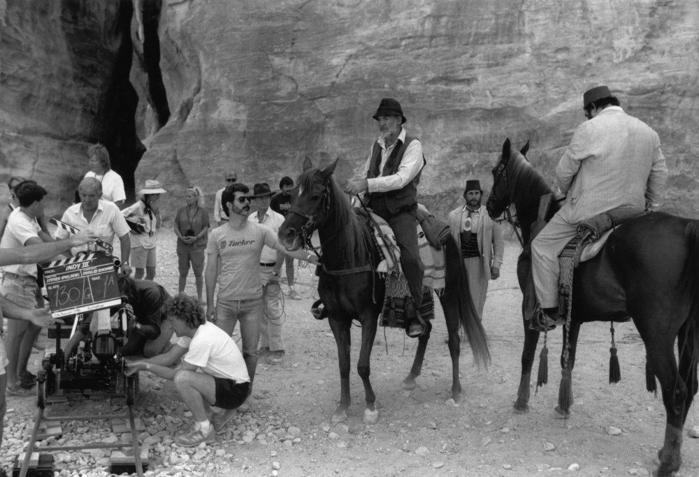 George Lucas readies a scene with Sean Connery and John Rhys-Davies on horseback in the canyon in Petra, Jordan for the third film, Indiana Jones and the Last Crusade (1989). Connery plays Indy's eccentric father, Professor Henry Jones, who is kidnapped by the Nazis for help in their search for the Holy Grail