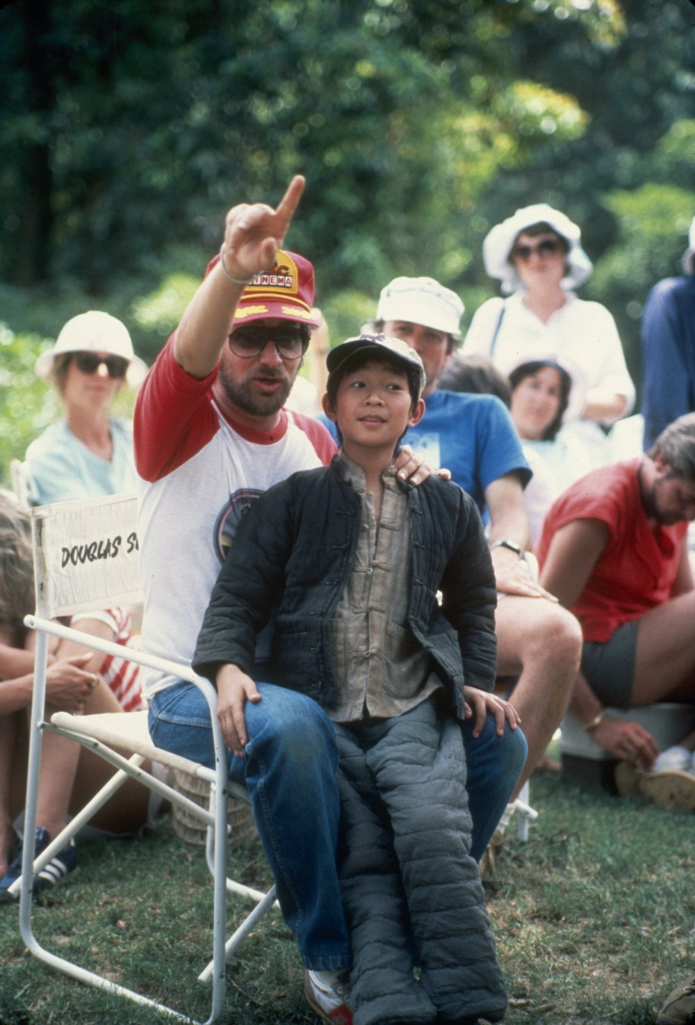 In cinematographer Douglas Slocombe's chair, Spielberg enjoys a moment in between takes with 12-year-old actor Ke Huy Quan (who plays Indy's sidekick Short Round) on location in India for the second film in the series, Indiana Jones and the Temple of Doom (1984)