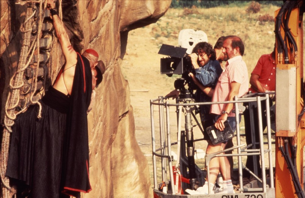 On a camera crane, Spielberg films a deadly skirmish on the remains of the rope bridge, hanging down the cliff edge