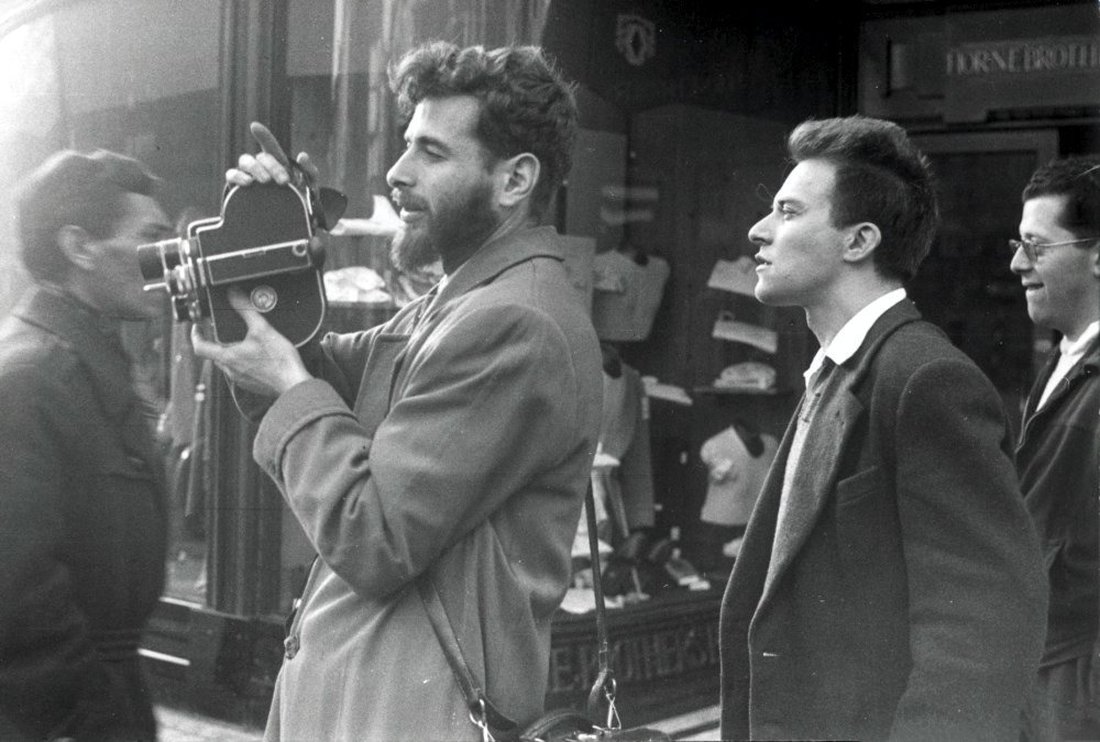 Walter Lassally with his 16mm Bolex camera shooting Refuge England (1949) with Robert Vas in London's West End