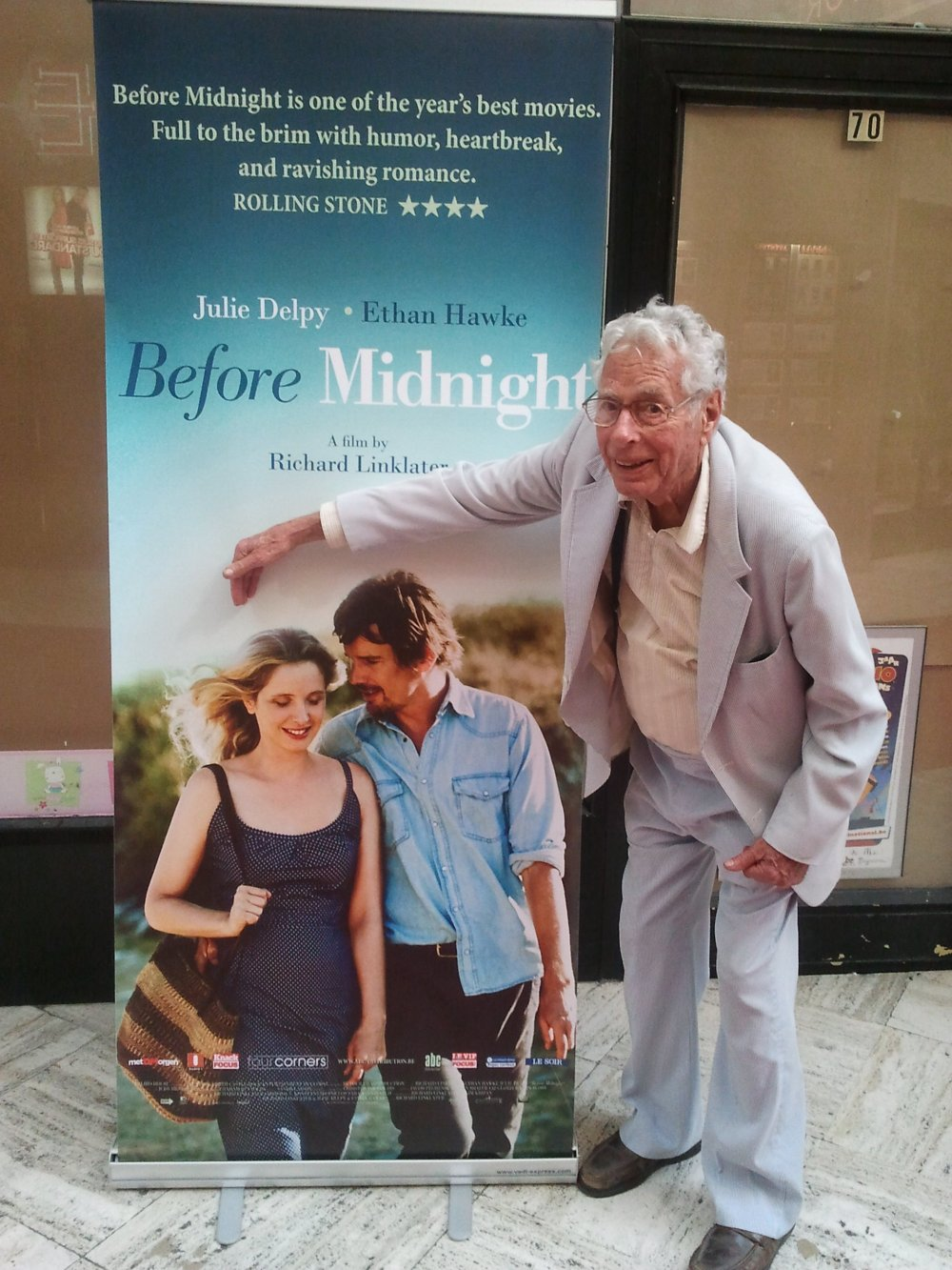 Walter Lassally in July 2013 in Brussels, posing in front a poster of Richard Linklater's Before Midnight (2013) in which he played an old British writer settled in Greece