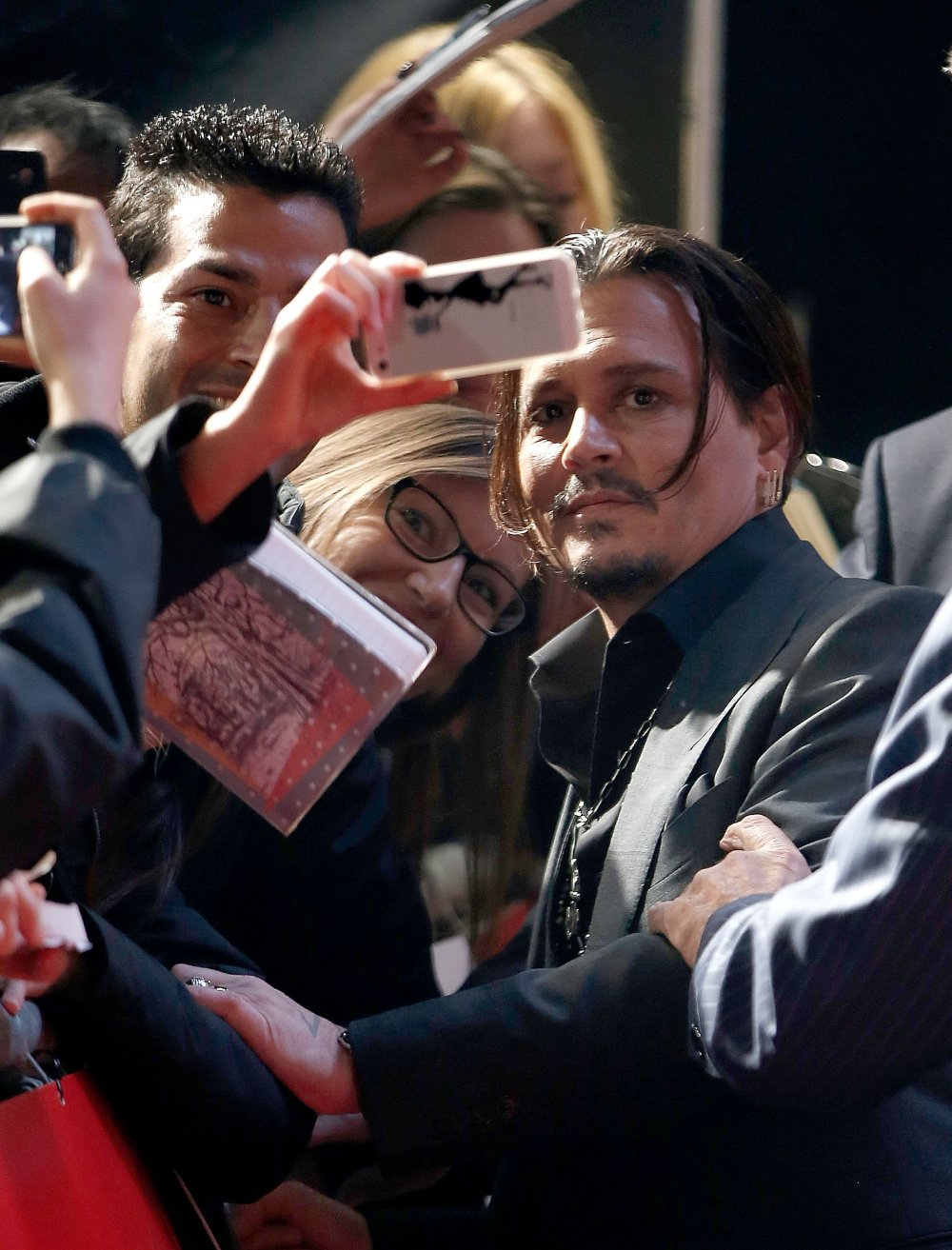 Johnny Depp poses for a camera on the red carpet for Black Mass