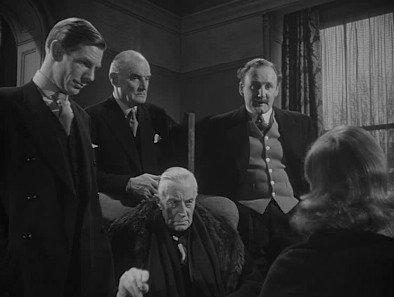 L to R: Michael Corland (Michael Gough), Mannering (Desmond Roberts), Sir John Kierlaw (Ernest Thesiger), Cranford (Howard Marion-Crawford), Daphne (Joan Greenwood)