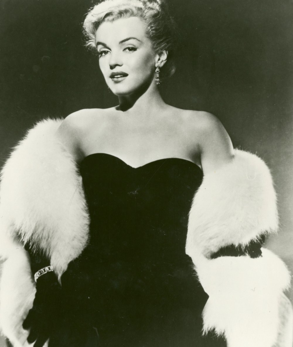 Promotional still of Marilyn Monroe with white fur and diamonds