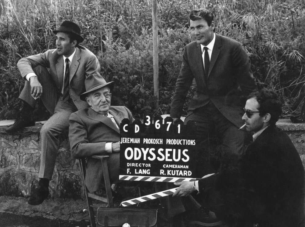 Holding the clapperboard for the fictional film-within-a-film directed by Fritz Lang (in the chair) in Le Mépris (1963). Michel Piccoli (left) plays the film's conflicted screenwriter, while Jack Palance (right) is its ruthless American producer