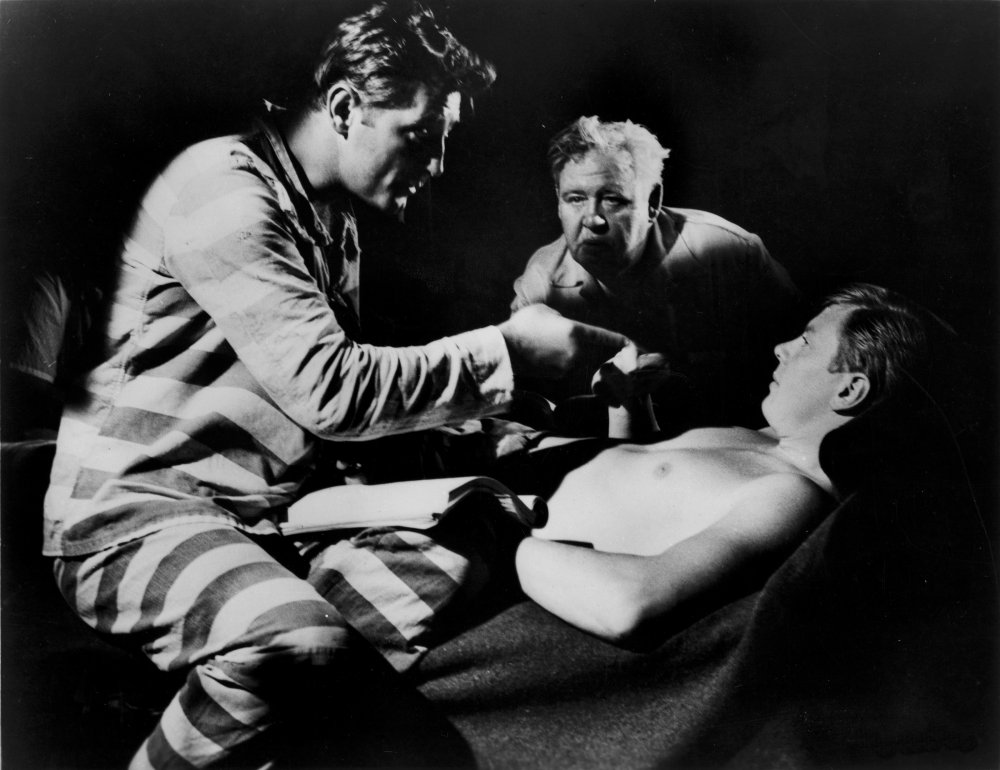 Laughton watches actors Robert Mitchum and Peter Graves getting ready for the early jail scene, where the film's terrifying villain discovers that a stolen fortune is hidden away awaiting recovery.
