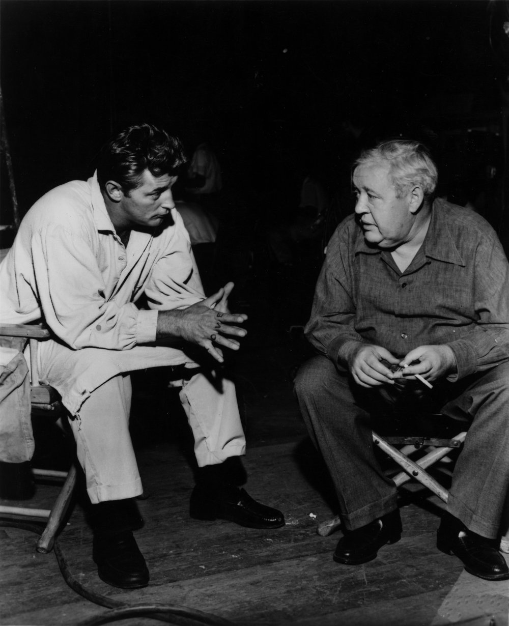 A conversation between Robert Mitchum and his director. Mitchum's character's sinister 'L.O.V.E.' tattoo is clearly visible on his right hand.