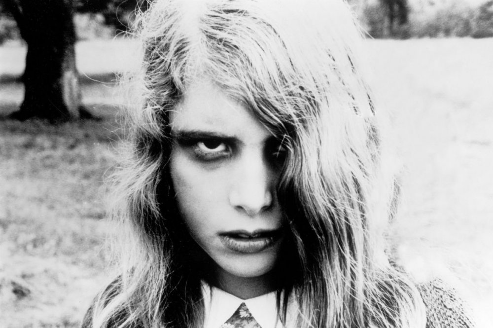 A young, undead woman, with dark circles around her eyes, her hair nearly covering one eye, staring blankly at the camera.