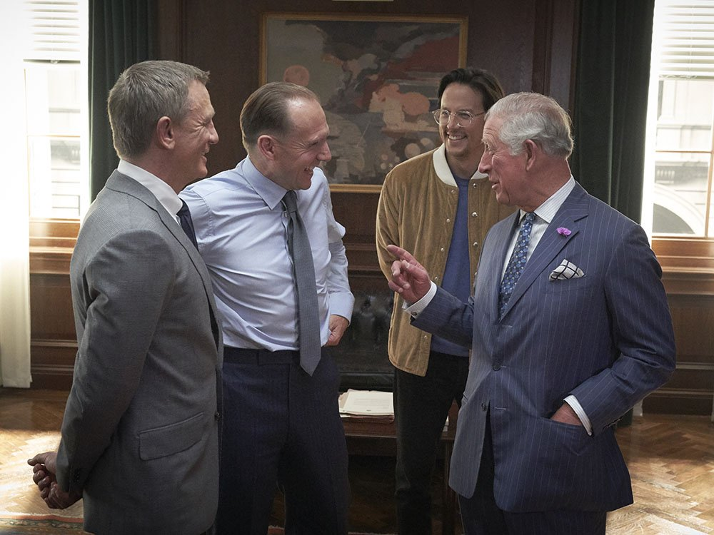 Actors Daniel Craig and Ralph Fiennes talk to Prince Charles, alongside director Cary Joji Fukunaga