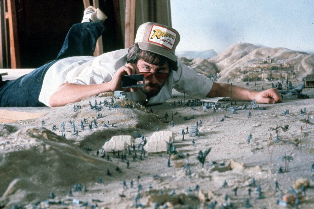 The 33-year-old Steven Spielberg gets down on the floor to survey a miniature desert base during the model work on Raiders of the Lost Ark (1981)