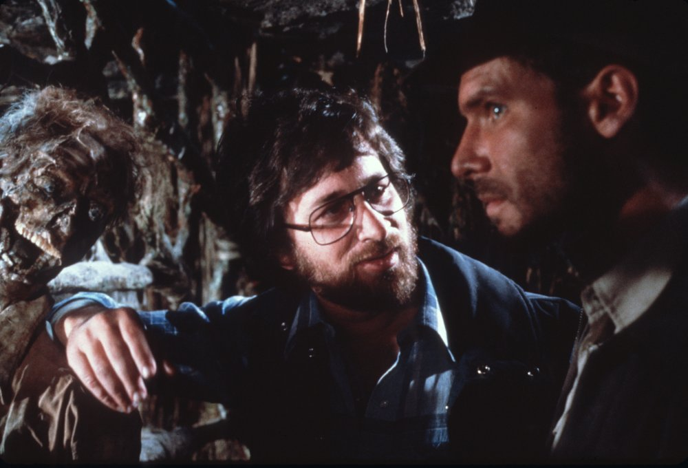 Spielberg chats with his star, Harrison Ford, while a decomposed friend looks on