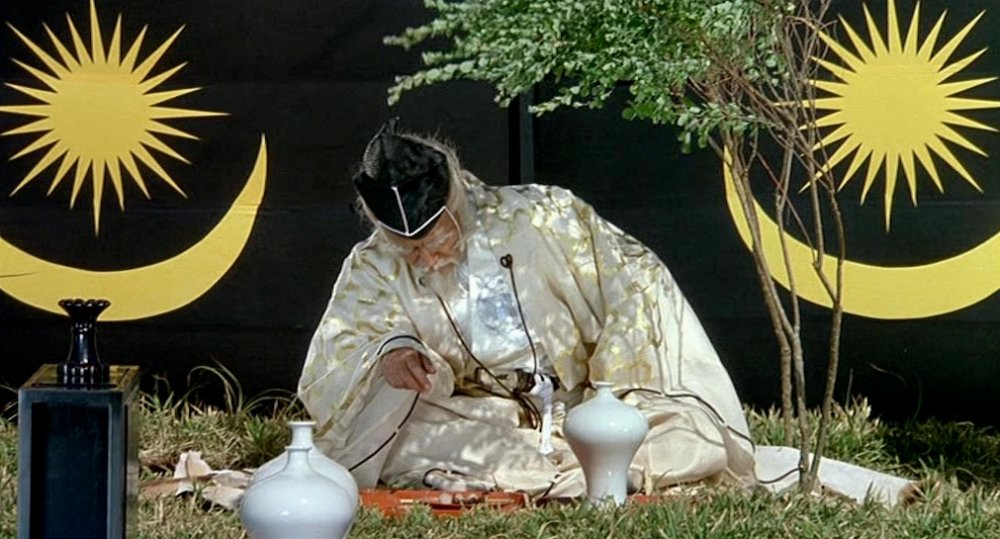 Having set up camp following the opening boar hunt, Lord Hidetora feigns sleep, overwhelmed by anger after his third son, Saburo, insultingly questions his judgement. The silence is accompanied by the rustling sound of wind picking up on the soundtrack, expressing his discontent before he banishes Saburo to live as an outlaw. Toru Takemitsu's score, consisting predominantly of traditional woodwind instruments, such as fue, sho and shakuhachi, is conspicuously absent in the film's first 20 minutes