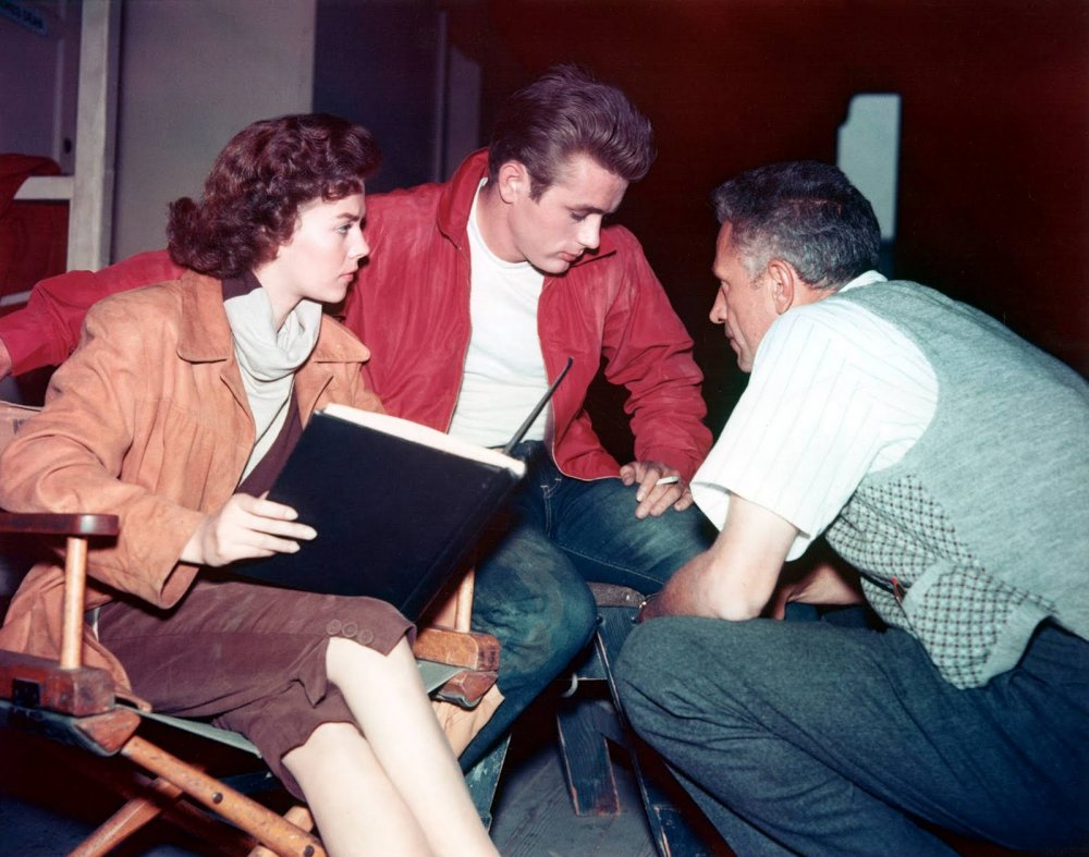 Stars Natalie Wood and James Dean, in that unforgettable red jacket, hear from director Nicholas Ray in a quiet moment between filming