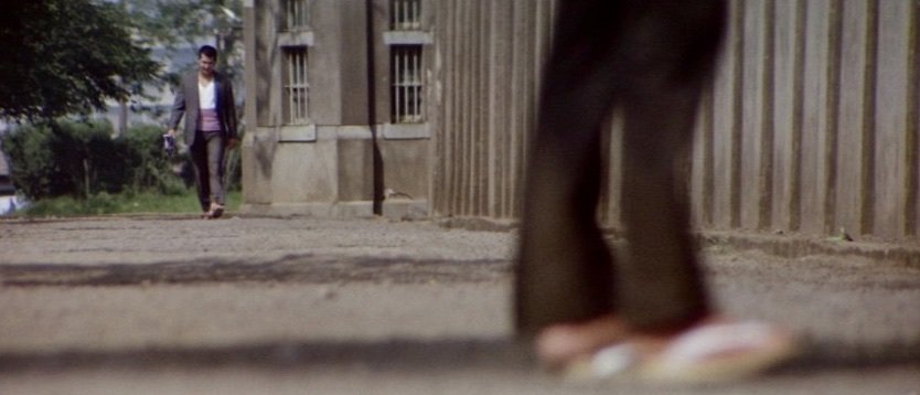In the style of an observational documentary, use of long lenses keeps the viewer at a detached distance throughout the film. Jiro's release from jail after taking an eight-year fall for his gang is an early example, in which the limited depth of field draws the spectator to look at the area of the screen that's in sharp focus