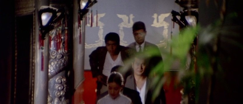The flattened perspectives often yield striking abstractions, with the bright green smudge of the foreground plant and the exotic décor of the Chinese restaurant as much features of the two-dimensional image as the characters within it