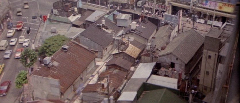Hasebe also makes abrupt switches to extreme wide shots, such as in this scene in which a tightly framed fistfight in the cramped back room of a shop moves into a narrow alley outside. The fighters are barely visible in the bottom right-hand corner of the frame. The implication is that this particular conflict is but one tiny, hidden part of the greater ongoing battle over who owns the capital's skyline