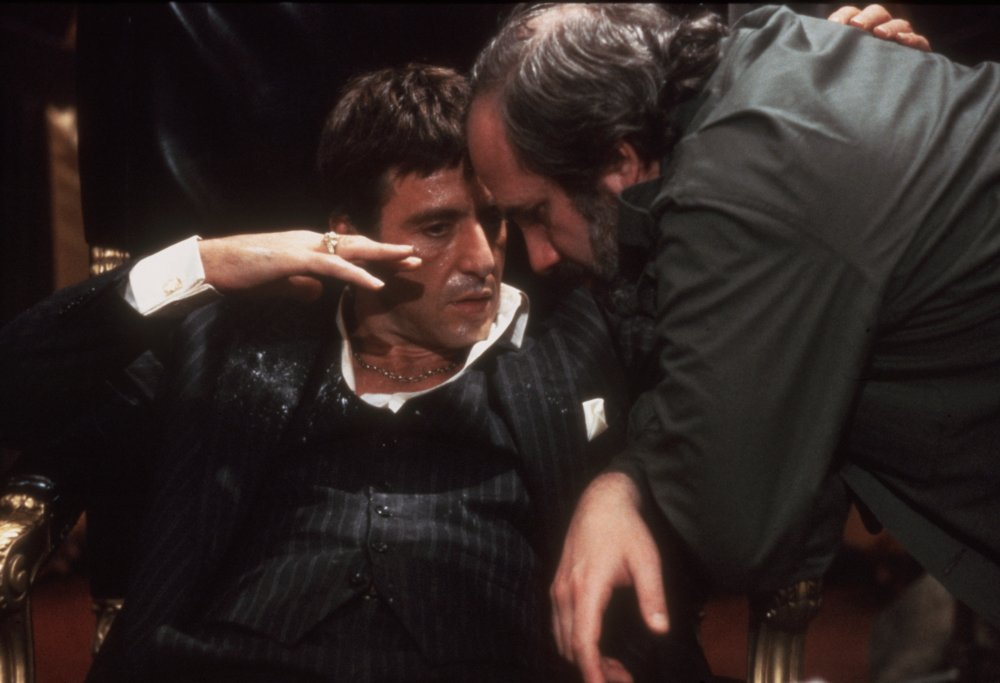 Al Pacino (as gangster Tony Montana) and director Brian De Palma have a tête-à-tête on the set of Scarface (1983)