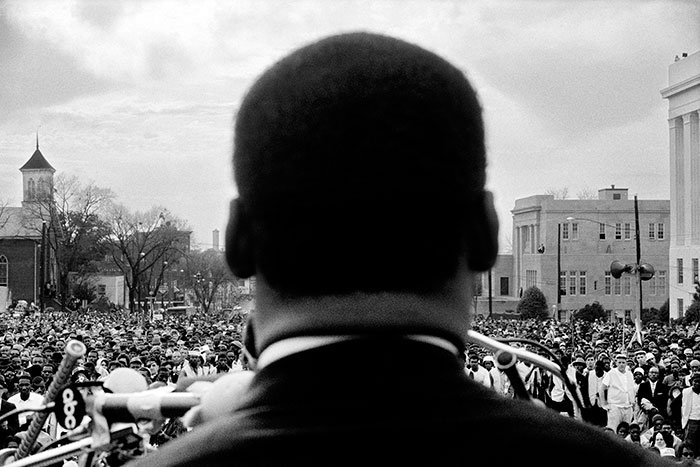 Dr. Martin Luther King, Jr. looks out at crowd in Montgomery, 1965