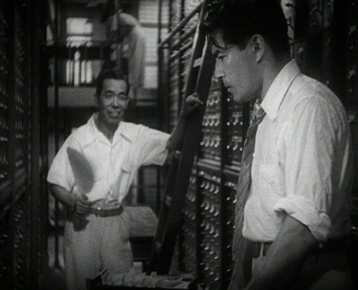 Kurosawa conveys the sweaty, high-pressure atmosphere throughout by way of characters continuously wafting themselves with fans or mopping their brows