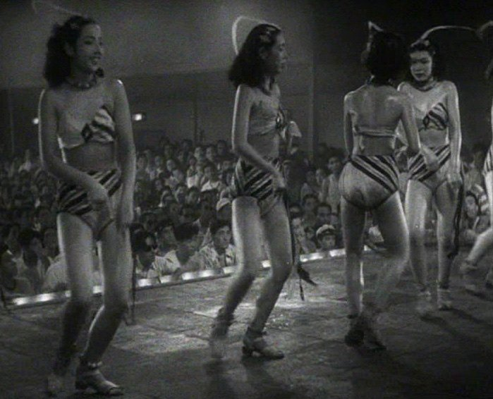 Sweat glistens on the bodies of the nightclub floorshow performers, among whom lies a key informant, while the audience continuously fan themselves in the background
