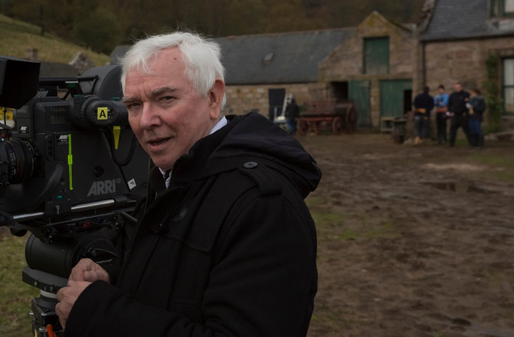 The director in the heavily trampled mud outside the Guthrie farmhouse