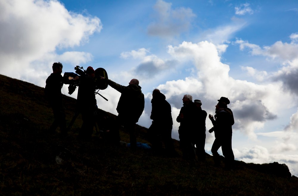 Preparing a scene on the hillside with Davies and his crew in silhouette