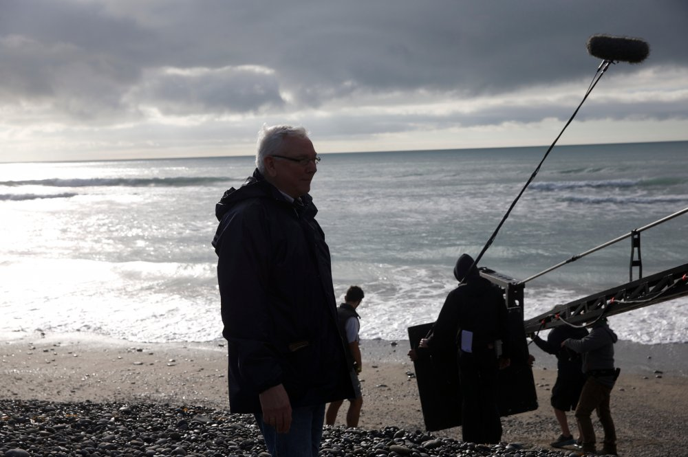 Davies against sunlight and lowering grey skies on the beach