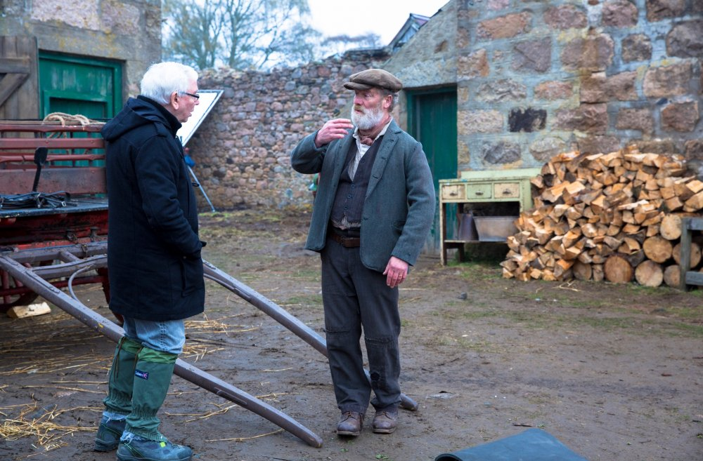 Director Terence Davies discusses a scene with Peter Mullan