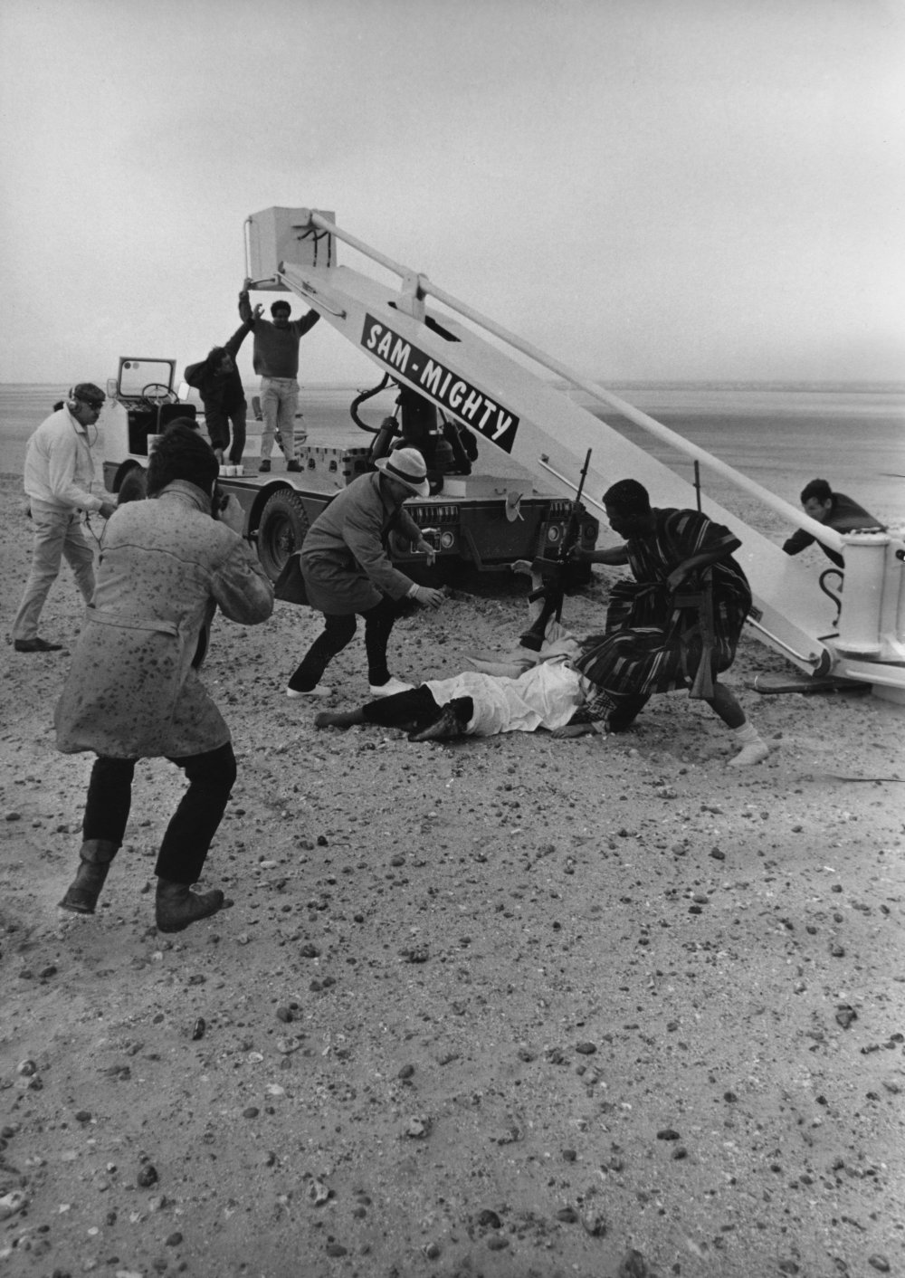 In the very final moments, Godard himself comes into shot running with the characters. He is the man wearing the beige mac and white hat. In the moment when Eve Democracy collapses, he is seen pouring red paint onto her body before it is hoisted up on the crane rig. The final shot of the film is Wiazemsky's body being lifted by this crane into the sky
