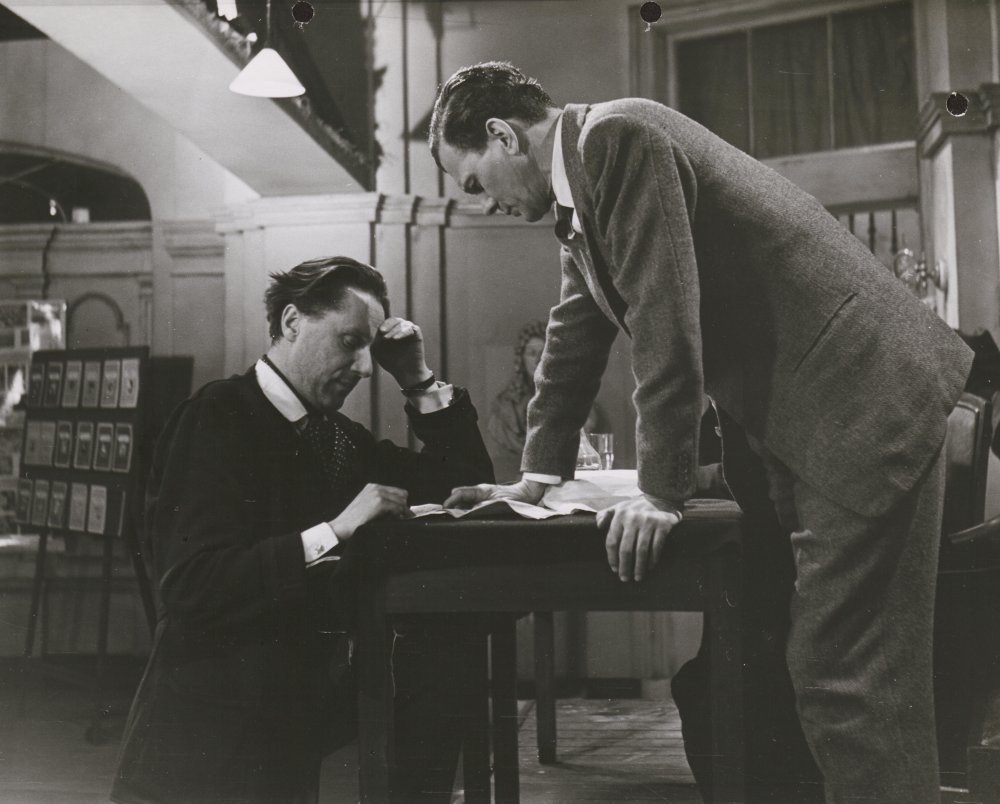 Carol Reed studying script pages with Joseph Cotten between scenes