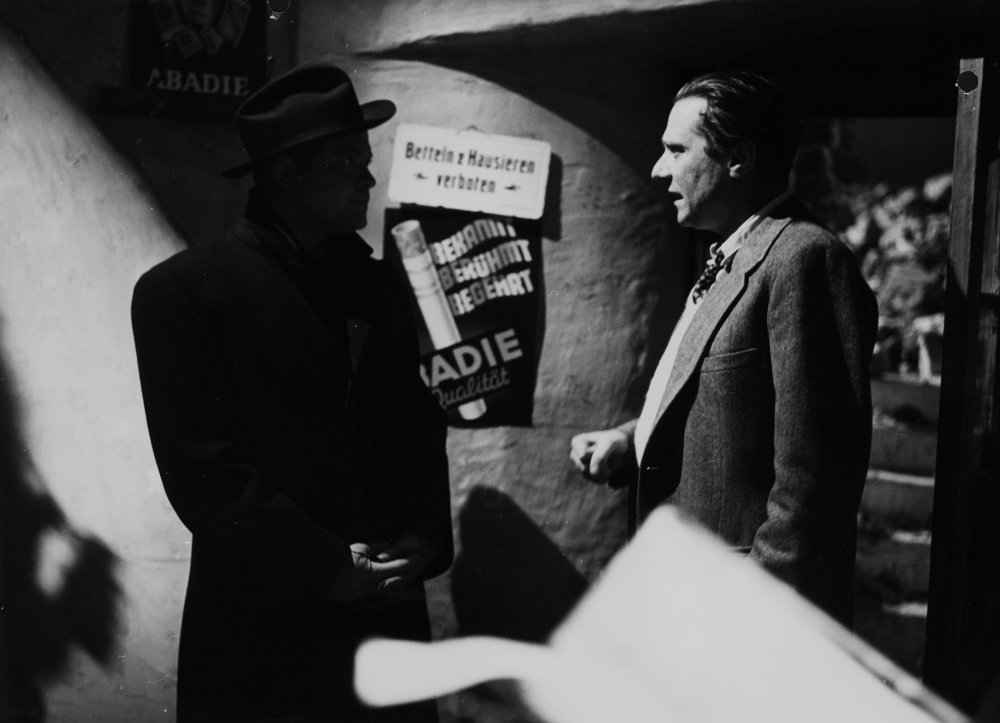 Shrouded in shadow, Orson Welles (playing racketeer Harry Lime) speaks with director Carol Reed during filming of the classic British thriller The Third Man (1949)